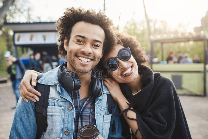 Dos viajeros afroamericanos felices con el peinado afro que abraza y que mira la cámara, haciendo la foto mientras que camina ade foto de archivo