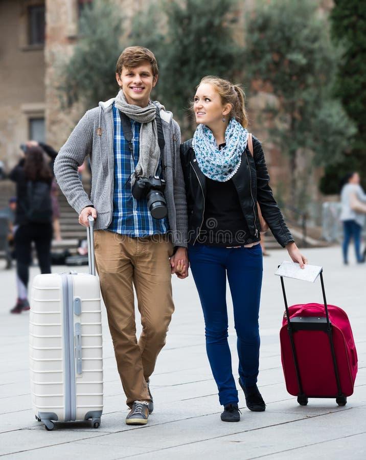 Dos viajeros con la cámara digital que caminan a través de la calle de la ciudad foto de archivo libre de regalías