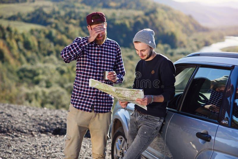 Dos viajeros de los amigos con el casquillo del té y de mirar el mapa de papel de encontrar manera correcta Hombres felices del i imagen de archivo libre de regalías
