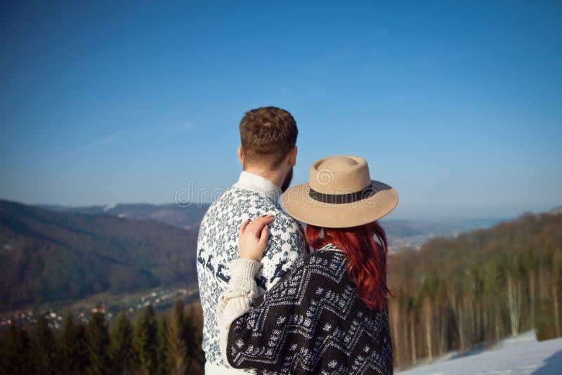 Dos viajeros jovenes que abrazan en las montañas fotografía de archivo