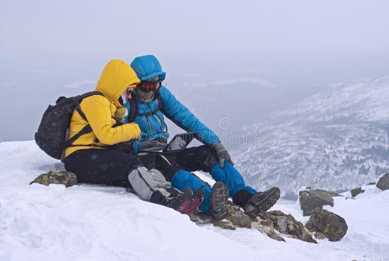 Dos viajeros que se sientan con un ordenador portátil en invierno encima de una montaña fotografía de archivo