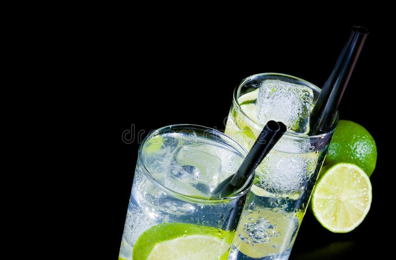 Dos vidrios con el cóctel y el hielo con la rebanada de la cal en la tabla negra imagenes de archivo