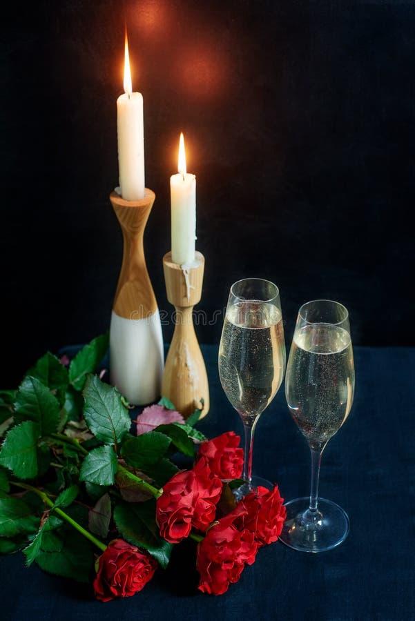 Dos vidrios con el champán blanco y un ramo de rosas rojas en el fondo de velas imagen de archivo