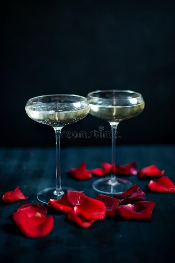 Dos vidrios con el champán y los pétalos blancos de rosas rojas en el fondo negro imagen de archivo