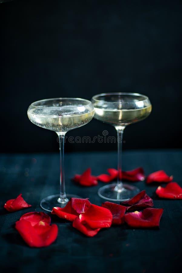 Dos vidrios con el champán y los pétalos blancos de rosas rojas en el fondo negro imagen de archivo libre de regalías