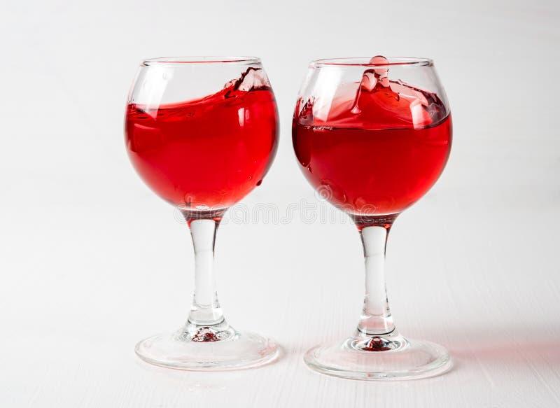 Dos vidrios con el jugo rojo, vino con diferente salpican fotografía de archivo