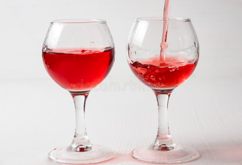 Dos vidrios con el jugo rojo, vino con diferente salpican fotografía de archivo libre de regalías