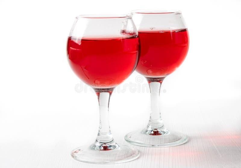 Dos vidrios con el jugo rojo, vino con diferente salpican fotos de archivo libres de regalías