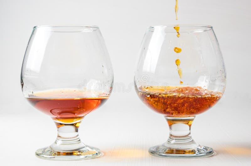 Dos vidrios con el jugo rojo, vino con diferente salpican imagenes de archivo