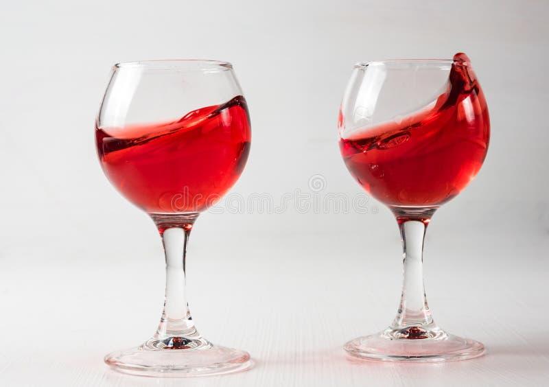 Dos vidrios con el jugo rojo, vino con diferente salpican imagen de archivo libre de regalías