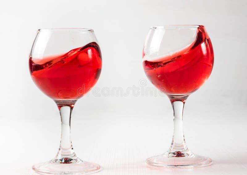 Dos vidrios con el jugo rojo, vino con diferente salpican foto de archivo