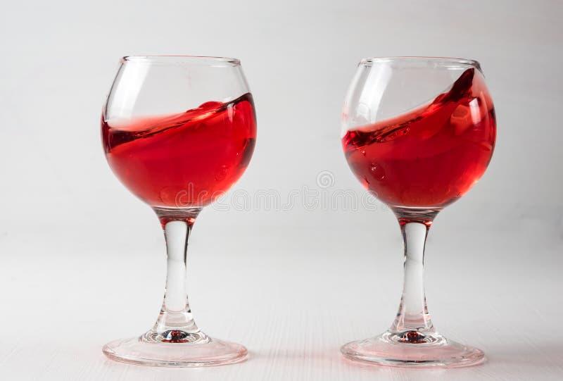 Dos vidrios con el jugo rojo, vino con diferente salpican imagen de archivo