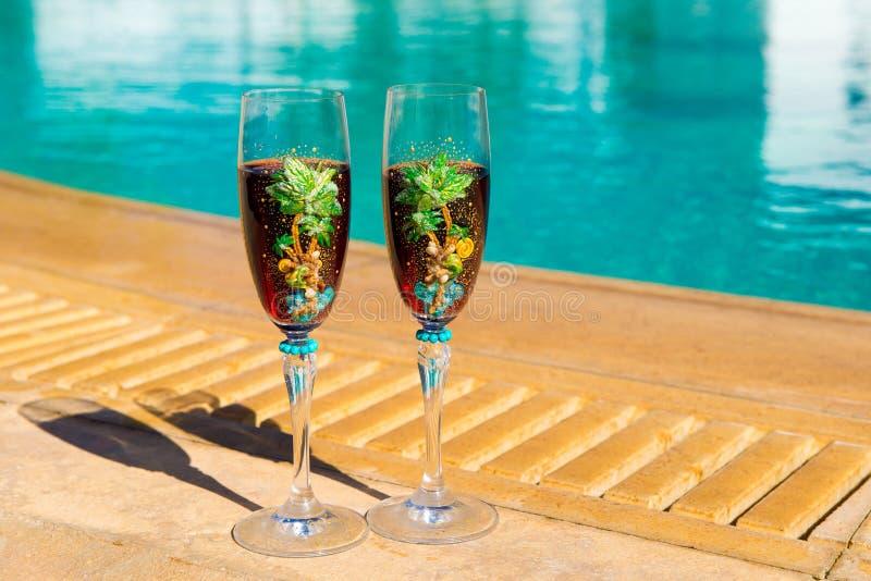 Dos vidrios con el vino en una tabla blanca cerca de la piscina imágenes de archivo libres de regalías