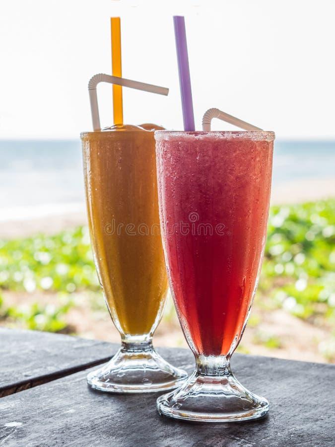 Dos vidrios con las bebidas frías en la tabla en el restaurante Smoothie del mango y de la sandía en las tazas de cristal en un r fotografía de archivo libre de regalías