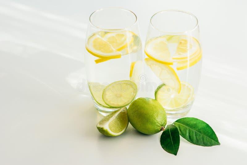 Dos vidrios con las rebanadas del agua, del hielo y del limón imagenes de archivo
