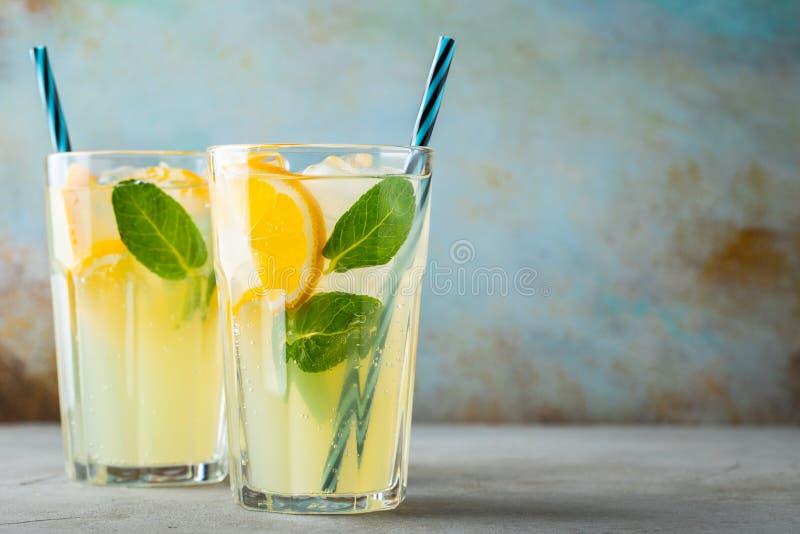 Dos vidrios con limonada o c?ctel del mojito con el lim?n y menta, bebida de restauraci?n fr?a o bebida con hielo en azul r?stico foto de archivo
