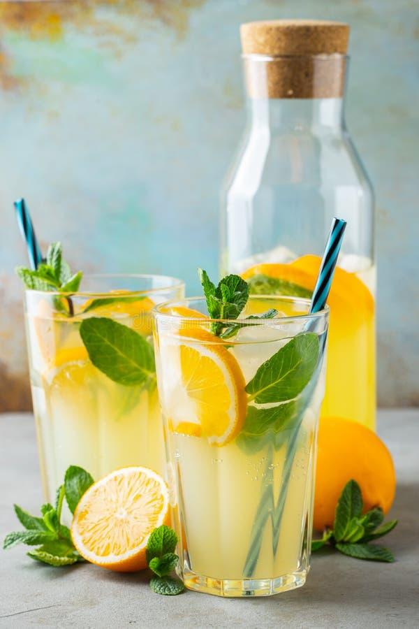 Dos vidrios con limonada o c?ctel del mojito con el lim?n y menta, bebida de restauraci?n fr?a o bebida con hielo en azul r?stico fotos de archivo