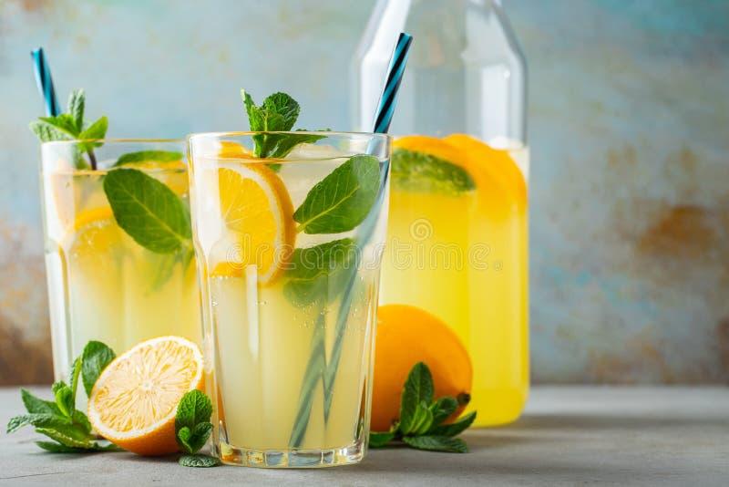 Dos vidrios con limonada o c?ctel del mojito con el lim?n y menta, bebida de restauraci?n fr?a o bebida con hielo en azul r?stico imagen de archivo libre de regalías