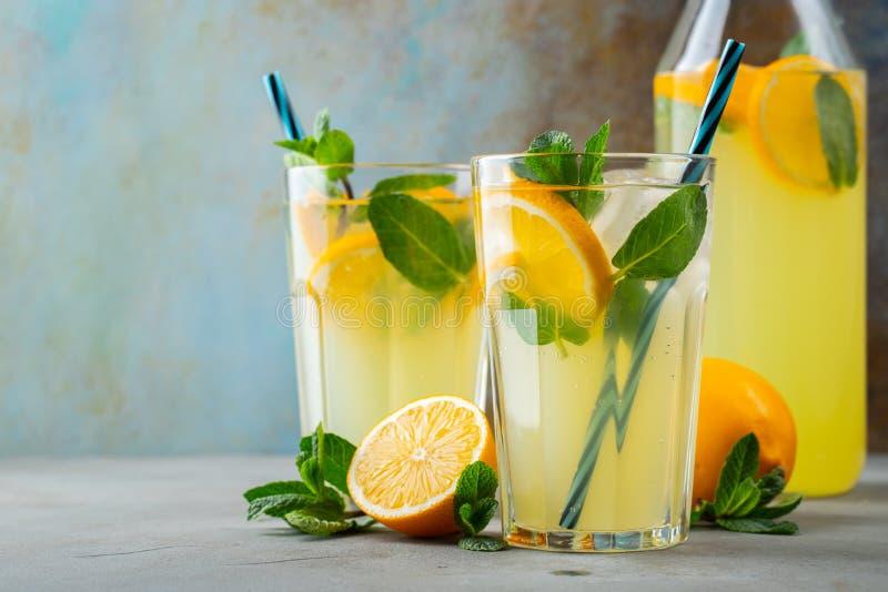 Dos vidrios con limonada o c?ctel del mojito con el lim?n y menta, bebida de restauraci?n fr?a o bebida con hielo en azul r?stico fotografía de archivo