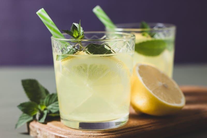 Dos vidrios con limonada o el cóctel del mojito con el limón y la menta imagen de archivo