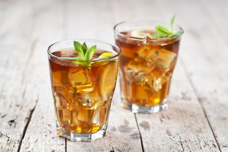 Dos vidrios con t? helado tradicional con el lim?n, las hojas de menta y los cubos de hielo en vidrio en la tabla de madera r?sti fotografía de archivo