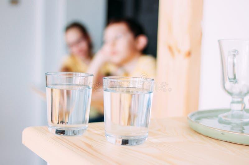 Dos vidrios de agua potable, niños en el fondo foto de archivo
