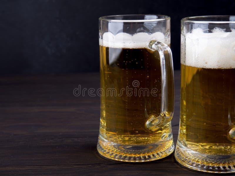 Dos vidrios de cerveza dorada sirvieron en los tablones de madera viejos, copyspace para el texto fotografía de archivo libre de regalías