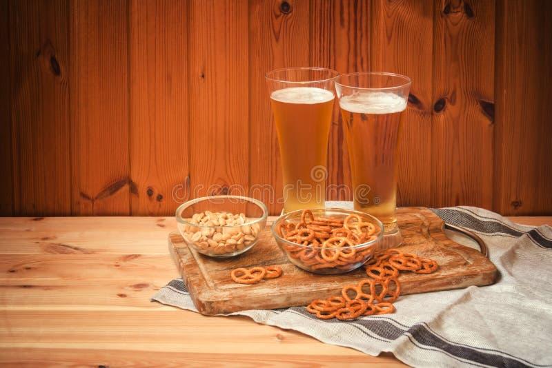 Dos vidrios de cerveza ligera con los pretzeles y los cacahuetes salados en la tabla de madera foto de archivo libre de regalías
