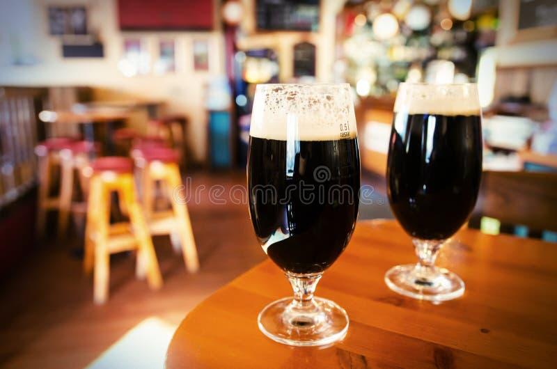 Dos vidrios de cerveza oscura en una barra foto de archivo