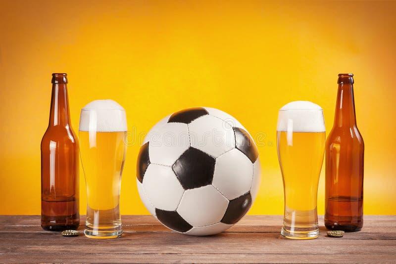 Dos vidrios de cerveza y de botellas acercan al balón de fútbol imágenes de archivo libres de regalías