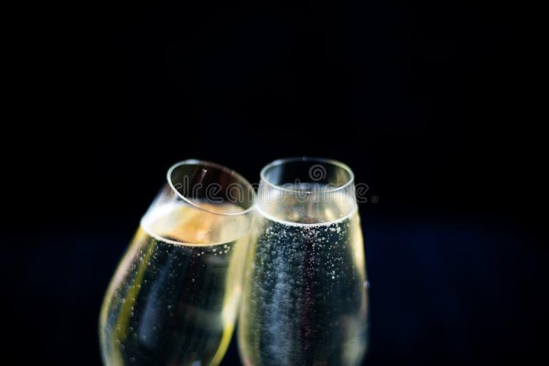 Dos vidrios de champán blanco en fondo negro foto de archivo libre de regalías