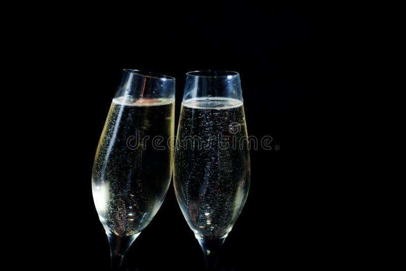 Dos vidrios de champán blanco en fondo negro fotos de archivo libres de regalías