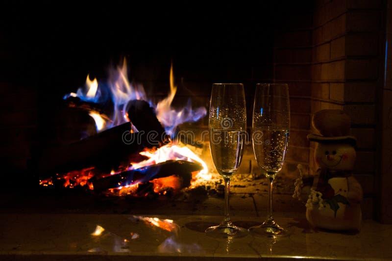 Dos vidrios de champán cerca de la chimenea foto de archivo libre de regalías