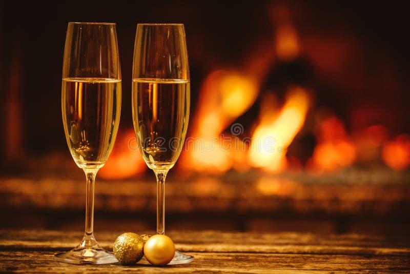 Dos vidrios de champán chispeante delante de la chimenea caliente C imagenes de archivo