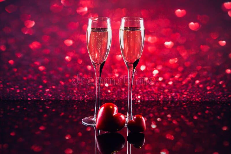 Dos vidrios de champán con el bokeh rojo de la forma del corazón en fondo imagenes de archivo