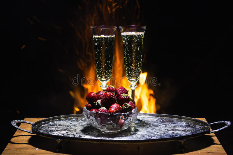 Dos vidrios de champán con la llama en fondo imagen de archivo libre de regalías
