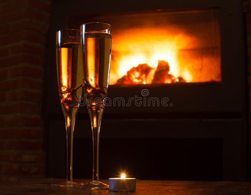 Dos vidrios de champán delante del fuego imagen de archivo libre de regalías