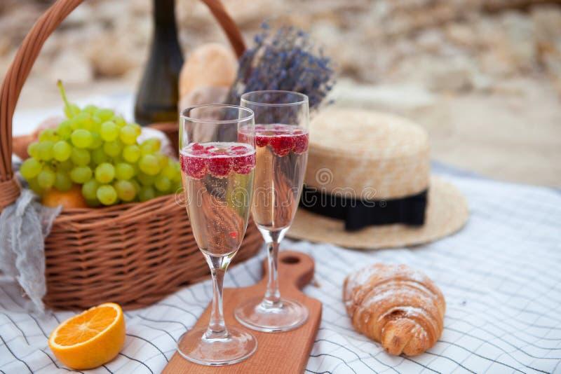 Dos vidrios de champán Meriende en el campo en la playa en la puesta del sol en el w imagenes de archivo