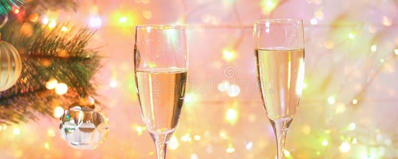 Dos vidrios de champán se colocan en una tabla de madera blanca en el fondo de un árbol y de guirnaldas del Año Nuevo Bokeh de la fotografía de archivo libre de regalías