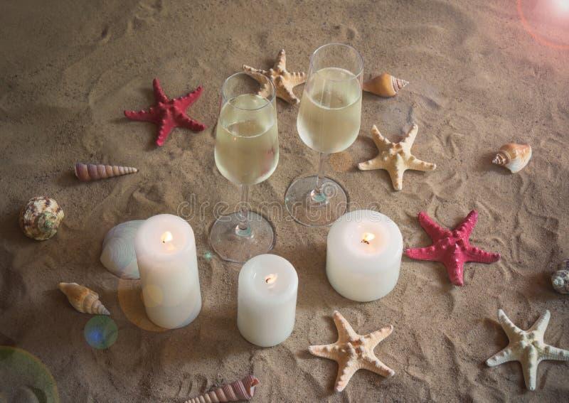Dos vidrios de champán, de velas, de cáscaras y de estrellas de mar en la playa de la arena imagenes de archivo