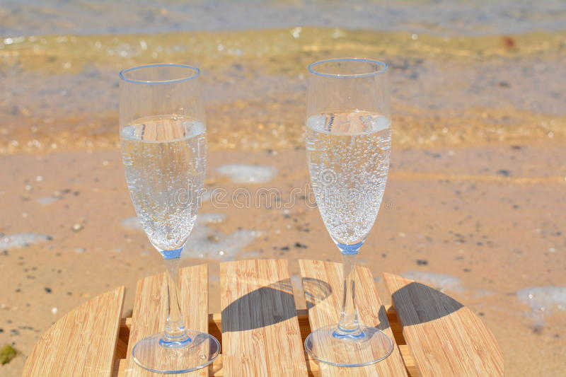 Dos vidrios de Champagne On The Beach imagenes de archivo