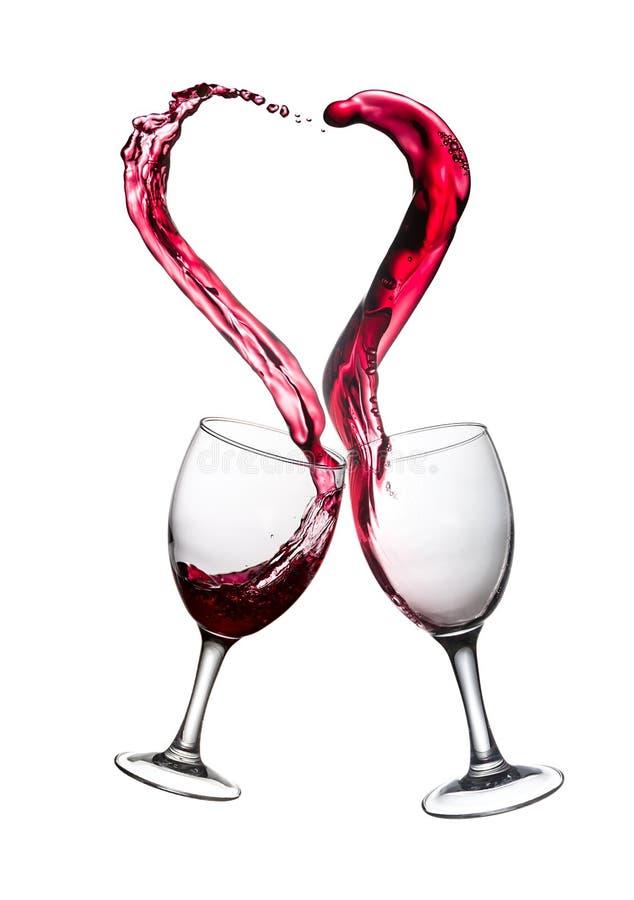 Dos vidrios de chapoteo del corazón del extracto del vino rojo imágenes de archivo libres de regalías
