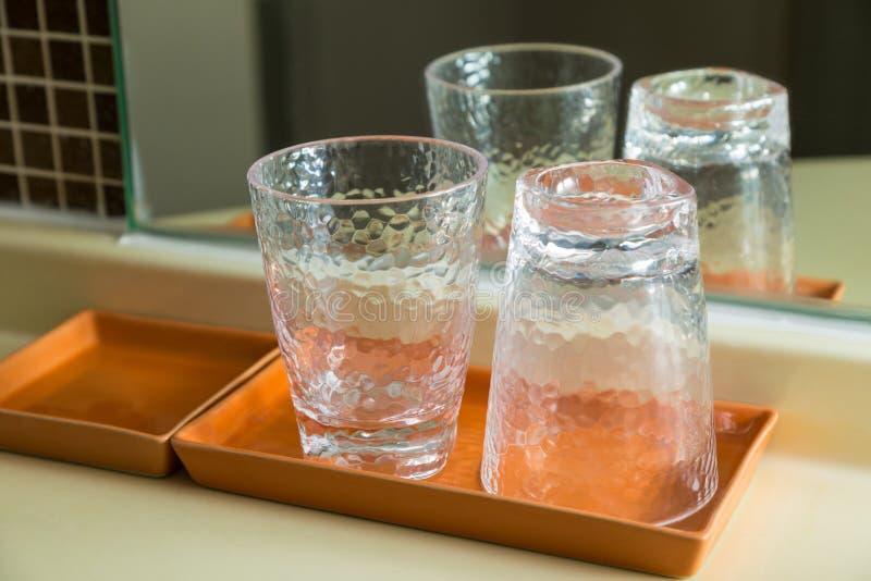 Dos vidrios de consumición claros en bandeja de cerámica marrón imagenes de archivo