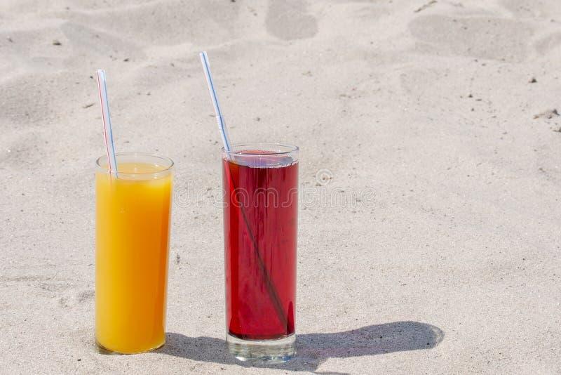 Dos vidrios de cristal con el jugo del mango y de la cereza con los túbulos Sandy Beach en un d?a de verano foto de archivo