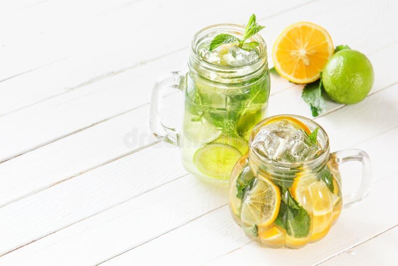Dos vidrios de cristal con limonada hecha en casa de la cal y del limón, fruta cítrica cortada en un fondo rústico de madera blan imagen de archivo