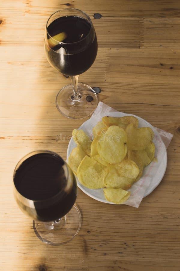 Dos vidrios de drik del vermú o de la cola y una placa de las patatas a la inglesa de patatas en una tabla de madera al día solea fotos de archivo