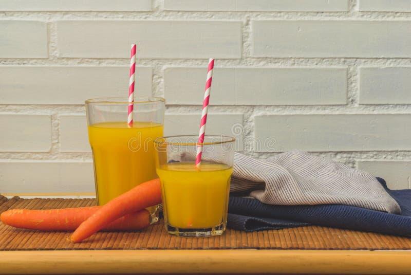 Dos vidrios de jugo de la naranja y de zanahoria y de paja de papel con el espacio para el texto de la copia foto de archivo