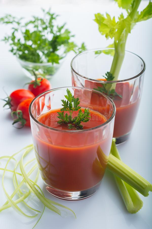 Dos vidrios de jugo de tomate con perejil y apio en el fondo blanco imagen de archivo