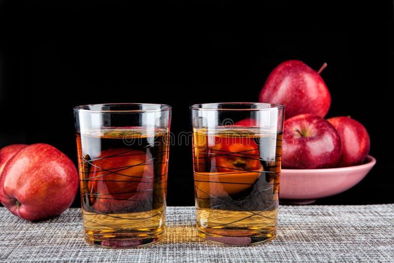Dos vidrios de jugo y de manzanas en un fondo negro imágenes de archivo libres de regalías