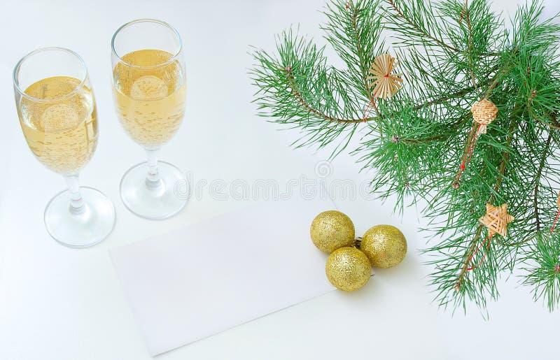 Dos vidrios de la hoja de papel en blanco blanca del champán Ramas de árbol de navidad y bolas de oro imagen de archivo